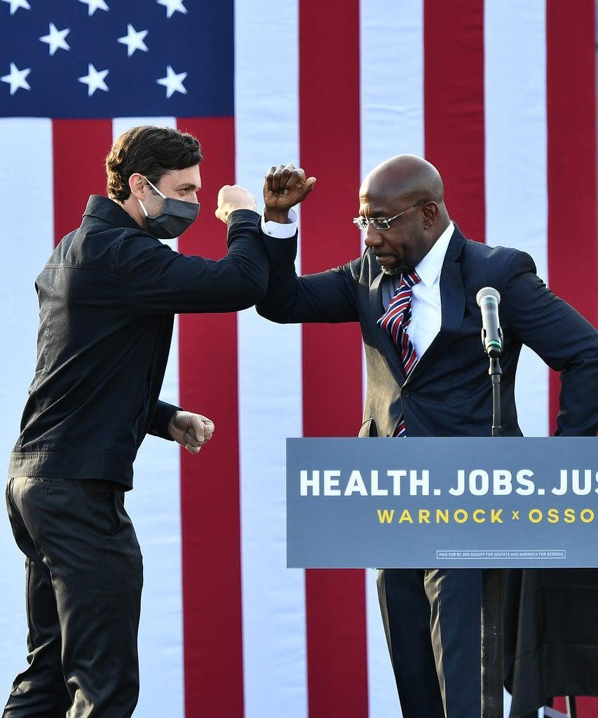 """STONECREST, GEORGIA – DECEMBER 28: Georgia Democratic Senate candidates Jon Ossoff and Raphael Warnock greet each other onstage during the """"Vote GA Blue"""" concert for Georgia Democratic Senate candidates Raphael Warnock and Jon Ossoff at New Birth Church on December 28, 2020 at New Birth Church in Stonecrest, Georgia. (Photo by Paras Griffin/Getty Images)"""