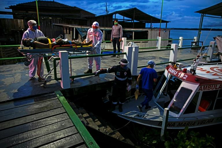 A resident of the Divino Espirito Santo community on the Pacaja River with COVID-19 symptoms is transported by boat-ambulance in a 12 hour trip to a municipal Hospital of the Portel area of Marajo island, in Brazil. (AFP Photo/TARSO SARRAF)