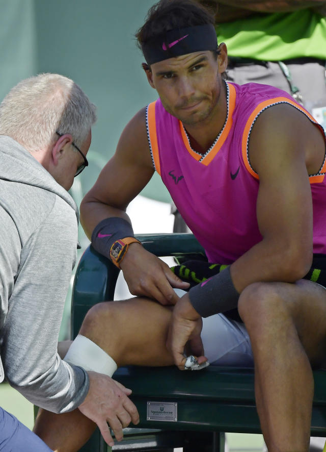 Rafael Nadal, of Spain, gets his knee wrapped by a trainer during his match against Karen Khachanov, of Russia, at the BNP Paribas Open tennis tournament Friday, March 15, 2019, in Indian Wells, Calif. (AP Photo/Mark J. Terrill)