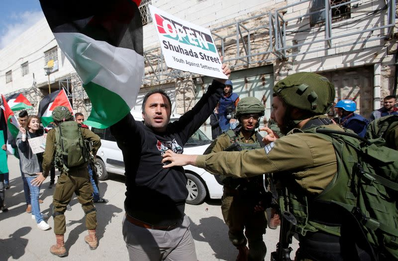 FILE PHOTO: Palestinian activist Issa Amro is pushed back by an Israeli solider during clashes in Hebron