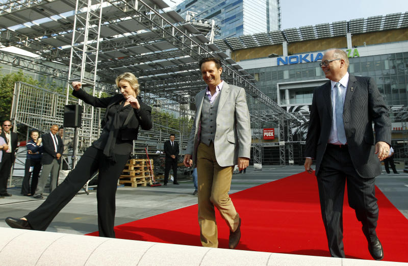 Actress Jane Lynch, left, executive producer Mark Burnett, center, and Academy of Television Arts and Sciences president John Shaffner rollout of the red carpet for the 63rd Primetime Emmy Awards in Los Angeles, Wednesday, Sept. 14, 2011.  The Emmy Awards will take place Sunday, Sept. 18 in Los Angeles. (AP Photo/Matt Sayles)