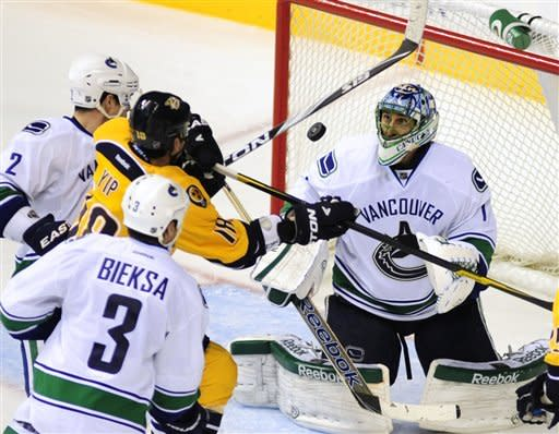 Vancouver Canucks goalie Roberto Luongo (1) eyes a loose puck in front of Canucks defenseman Dan Hamhuis (2), Nashville Predators forward Brandon Yip (18) and Canucks defenseman Kevin Bieksa (3) in the third period of an NHL hockey game on Tuesday, Feb. 7, 2012, in Nashville, Tenn. (AP Photo/Mike Strasinger)