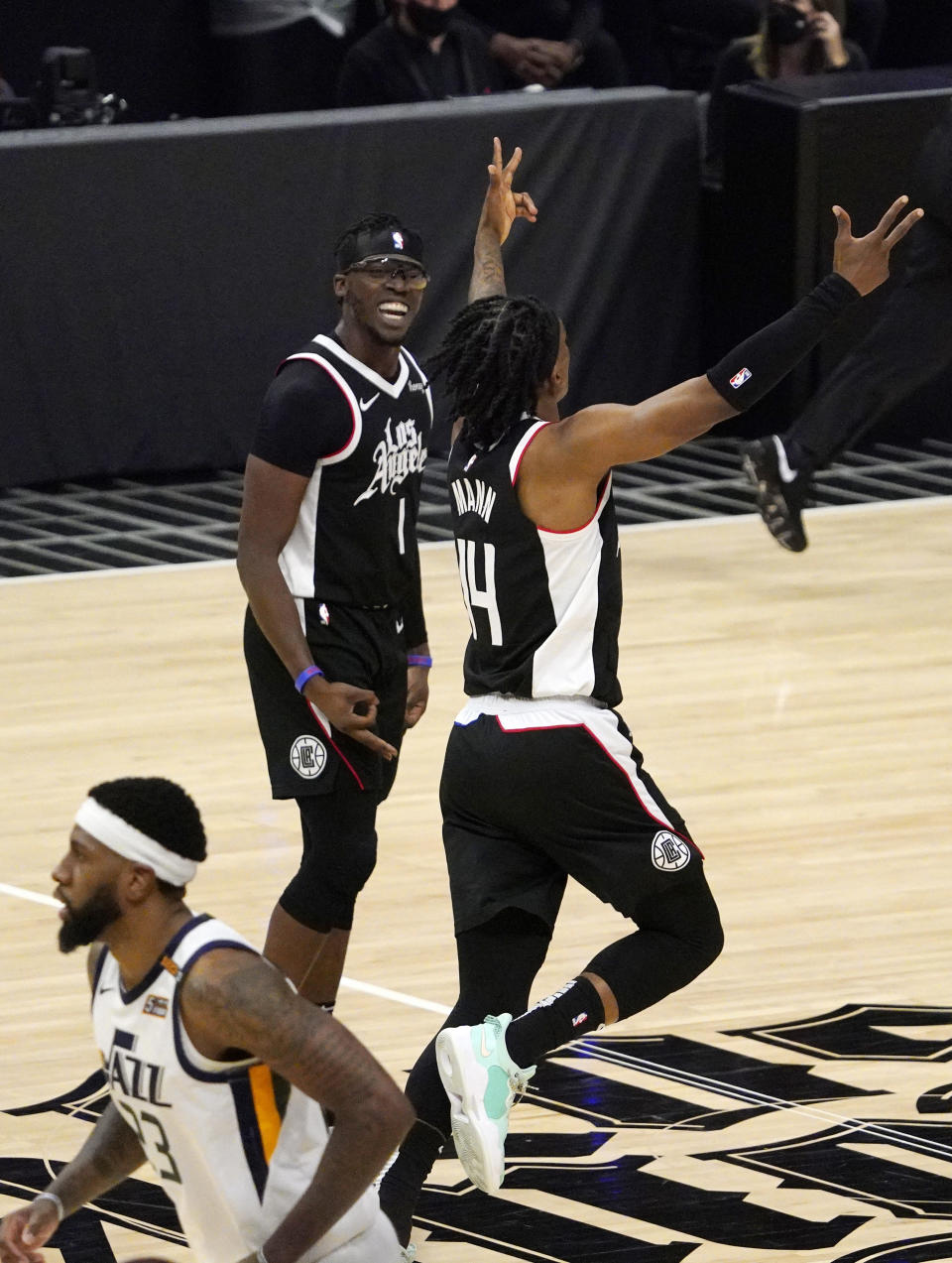 Los Angeles Clippers guard Reggie Jackson, upper left, and guard Terance Mann, right, celebrate after the Clippers scores as Utah Jazz forward Royce O'Neale stands, below, during the second half in Game 6 of a second-round NBA basketball playoff series Friday, June 18, 2021, in Los Angeles. (AP Photo/Mark J. Terrill)