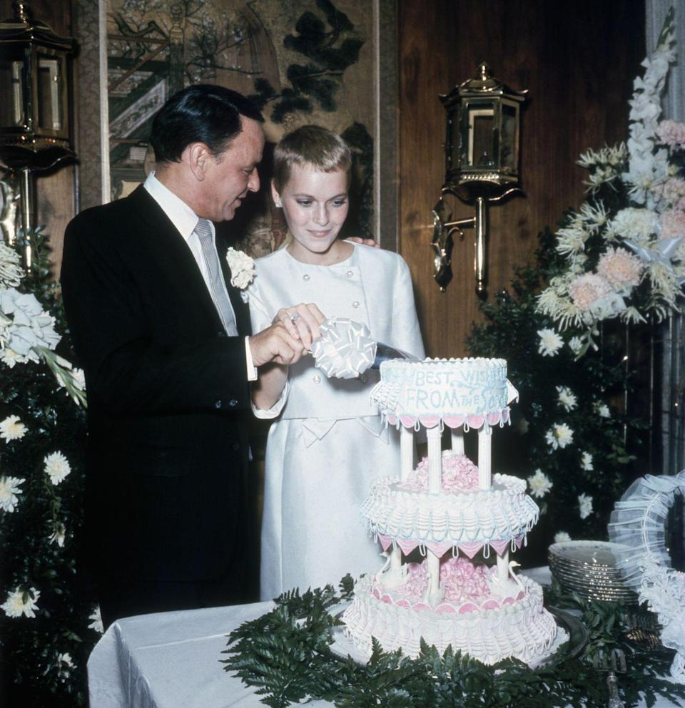 <p>Frank Sinatra looks over at actress Mia Farrow as they slice the cake following their wedding at the Sands Hotel on July 19th, 1966. The pair divorced in 1968 and Farrow married composer André Previn in 1970—divorcing in 1979. The union between Farrow and Sinatra was the third for the classical singer. He went on to marry once more, in 1976, to showgirl Barbara Blakeley. They stayed together until he passed in 1998.</p>