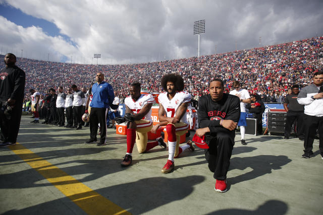 Colin Kaepernick (middle) and two teammates kneel during the national anthem last December before a football game in Los Angeles. (Michael Zagaris via Getty Images)