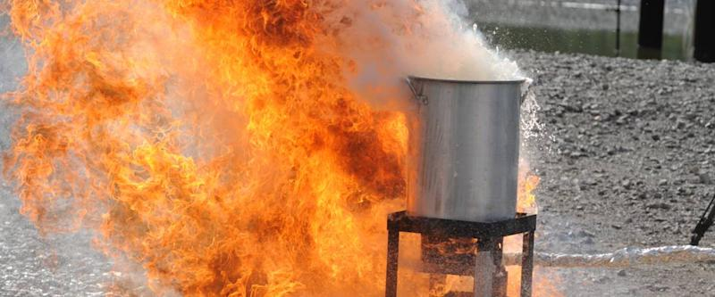 A raging fire occurs after a frozen turkey is placed in an over filled turkey fryer during a safety demonstration.