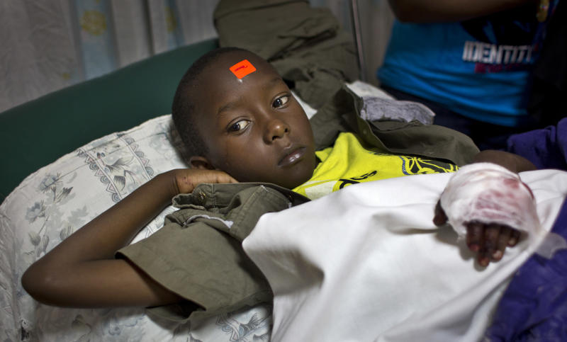 Malcolm Murage, 9, whose left hand was injured in an explosion at a Sunday school class and who wears an orange triage label on his forehead, is treated in Kenyatta National Hospital in Nairobi, Kenya Sunday, Sept. 30, 2012. An explosive device set off in a Sunday school class killed one child and seriously wounded three, according to Nairobi's acting police chief, who said said he suspects sympathizers with the Somali militant group al-Shabab were behind the attack at the Anglican church. (AP Photo/Ben Curtis)