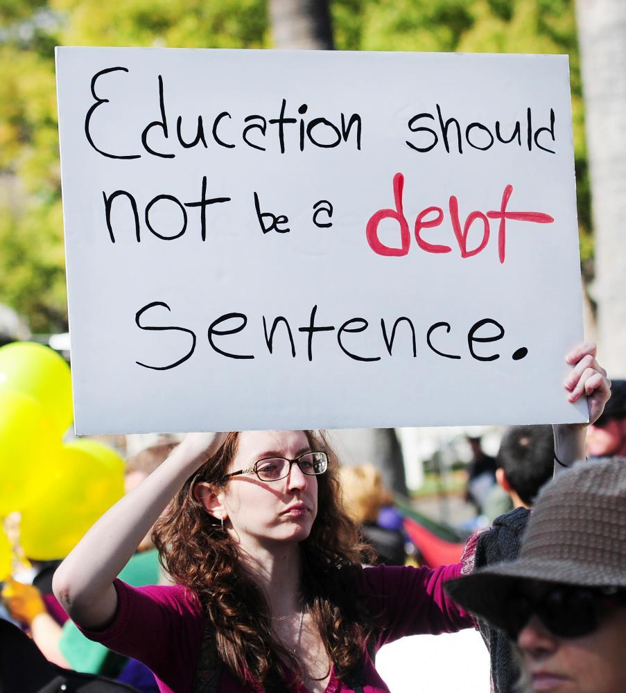 A young activist holding a sign at a protest against annual tuition hikes.