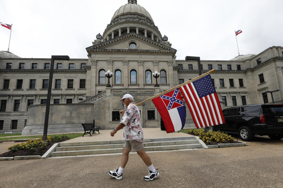 File-This June 27, 2020, file photo shows Don Hartness of Ellisville, Miss., walking around the Capitol carrying the current Mississippi state flag and the American flag in Jackson, Miss. Mississippi will surrender the Confederate battle emblem from its state flag, more than a century after white supremacist legislators embedded it there a generation after the South lost the Civil War. Mississippi's House and Senate voted in succession Sunday, June 28, 2020, to retire the flag, with broad bipartisan support. Republican Gov. Tate Reeves has said he will sign the bill, and the state flag would lose its official status as soon as he signs the measure. (AP Photo/Rogelio V. Solis, File)
