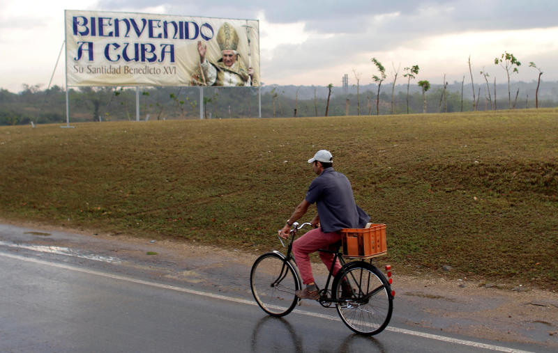 A man rides his bike along the road that connects Havana to the airport where a sign stands welcoming Pope Benedict XVI to Cuba in Havana, Cuba, early Monday March 26, 2012. Pope Benedict XVI arrives to Cuba on Monday afternoon. (AP Photo/Franklin Reyes)