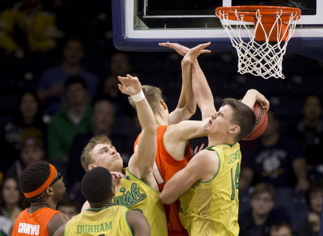 Syracuse's Marek Dolezaj, center, competes for a rebound with Notre Dame's Dane Goodwin and Nate Laszewski (14) during the first half of an NCAA college basketball game Saturday, Jan. 5, 2019, in South Bend, Ind. (AP Photo/Robert Franklin)