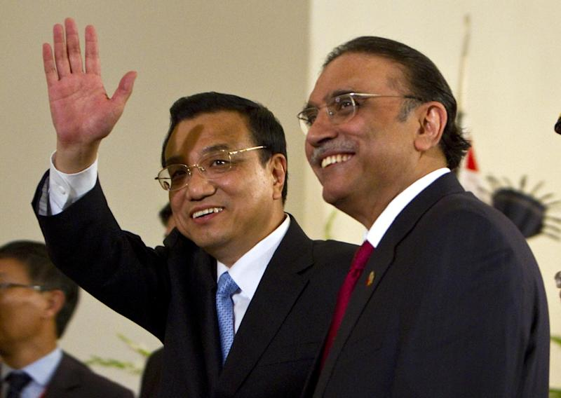 Visiting Chinese Premier Li Keqiang, left, waves as he leves with Pakistani President Asif Ali Zardari, right, after their joint press conference in Islamabad, Pakistan on Wednesday, May 22, 2013. China's premier began a two-day visit to Pakistan by praising the relationship between the two Asian powers in glowing terms.  (AP Photo/Anjum Naveed)