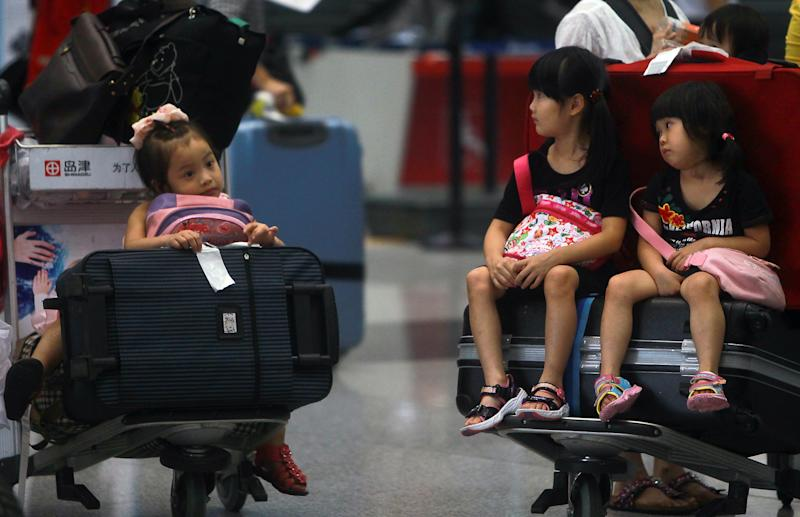 Children sit on the luggage carts as they stranded at the Beijing Capital International Airport after flights are canceled due to the heavy rains in Beijing, China Saturday, July 21, 2012. Heavy downpour flooded roads and caused hundreds of flights to be canceled in the capital. (AP Photo) CHINA OUT