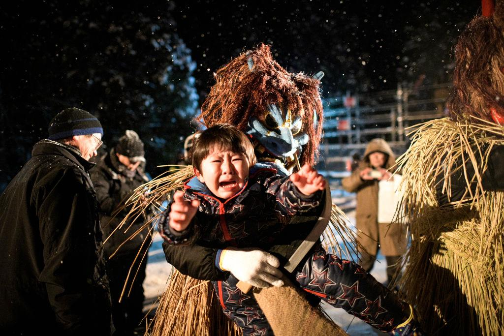 <p>A child cries while being lifted by men disguised as 'Namahage' wearing a demon like mask and a costume made of straw in Oga, Akita Prefecture, Japan, on Feb. 10, 2019. Namahage, considered divine messengers bringing blessings to people, visit houses in the area every New Year's Eve, yelling and telling children they have to behave themselves in a tradition designated as one of Japan's important intangible cultural assets. (Photo from Richard Atrero de Guzman/Nur Photo) </p>