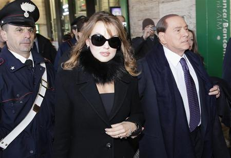 Former Italian PM Berlusconi and his fiancee Pascale walk at the Rome train station
