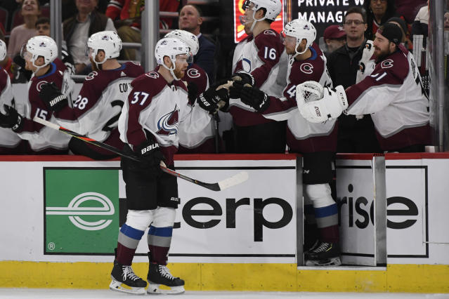 Colorado Avalanche's J.T. Compher (37) celebrates with teammates on the bench after scoring during the second period of an NHL hockey game against the Chicago Blackhawks, Friday, Nov. 29, 2019, in Chicago. (AP Photo/Paul Beaty)