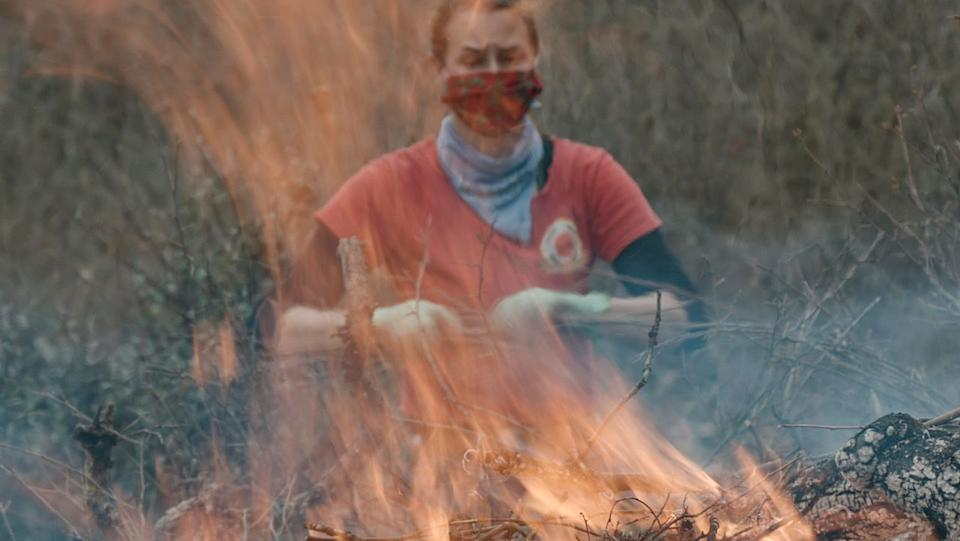 Stephanie Beard, the communication specialist for the conservation nonprofit Pepperwood, throws more dried brush on a flaming burn pile. (Photo: Ed Kashi/VII)