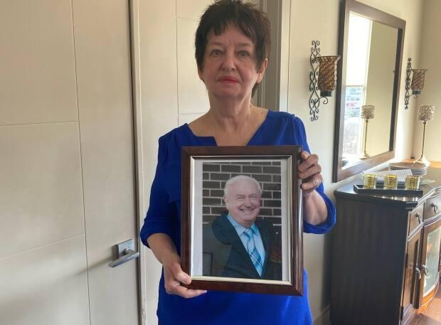 Anne MacPhee holds a portrait of her husband, Kelly, in their Halifax home. Kelly died in September from a heart attack while waiting for an ambulance to arrive. (Brian MacKay/CBC - image credit)