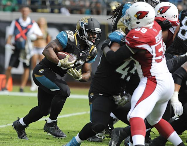 Jacksonville Jaguars running back Maurice Jones-Drew (32) charges past the Arizona Cardinals defense, including linebacker Marcus Ben,ard (59) for a 1-yard touchdown during the first half of an NFL football game in Jacksonville, Fla., Sunday, Nov. 17, 2013. (AP Photo/Stephen Morton)