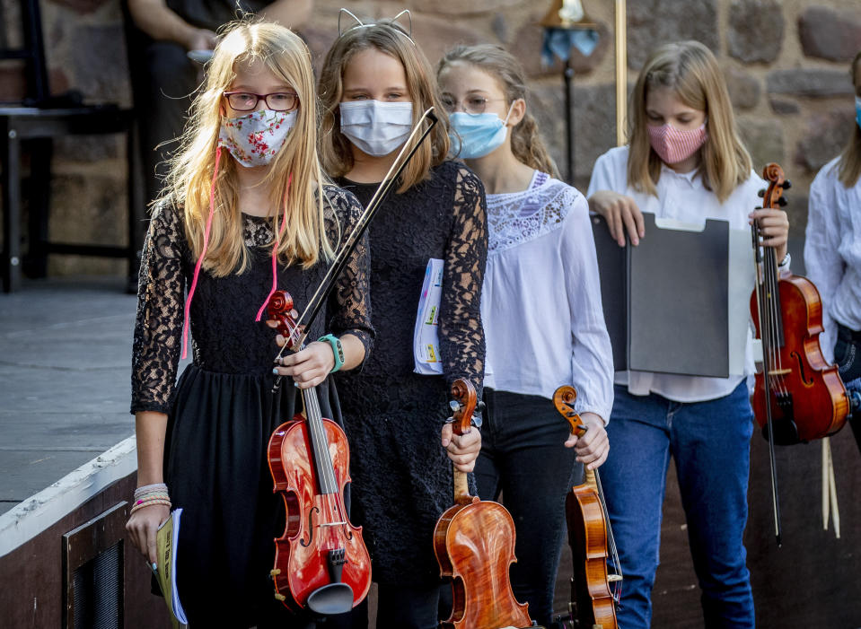 Young violinists wear face masks on the way to their music school concert in the old castle in Bad Vilbel near Frankfurt, Germany, Sunday, Sept. 20, 2020. (AP Photo/Michael Probst)