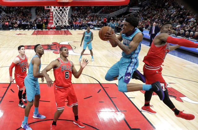 Charlotte Hornets' Malik Monk, second from right, flies past Chicago Bulls' David Nwaba for a dunk during the second half of an NBA basketball game Tuesday, April 3, 2018, in Chicago. The Bulls won 120-114. (AP Photo/Charles Rex Arbogast)