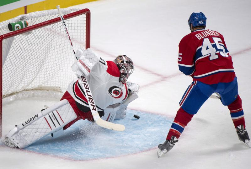 Carolina Hurricanes goaltender Anton Khudobin, left, makes a save against Montreal Canadiens' Michael Blunden during the first period of a preseason NHL hockey game Saturday, Sept. 21, 2013, in Montreal. (AP Photo/The Canadian Press, Graham Hughes)
