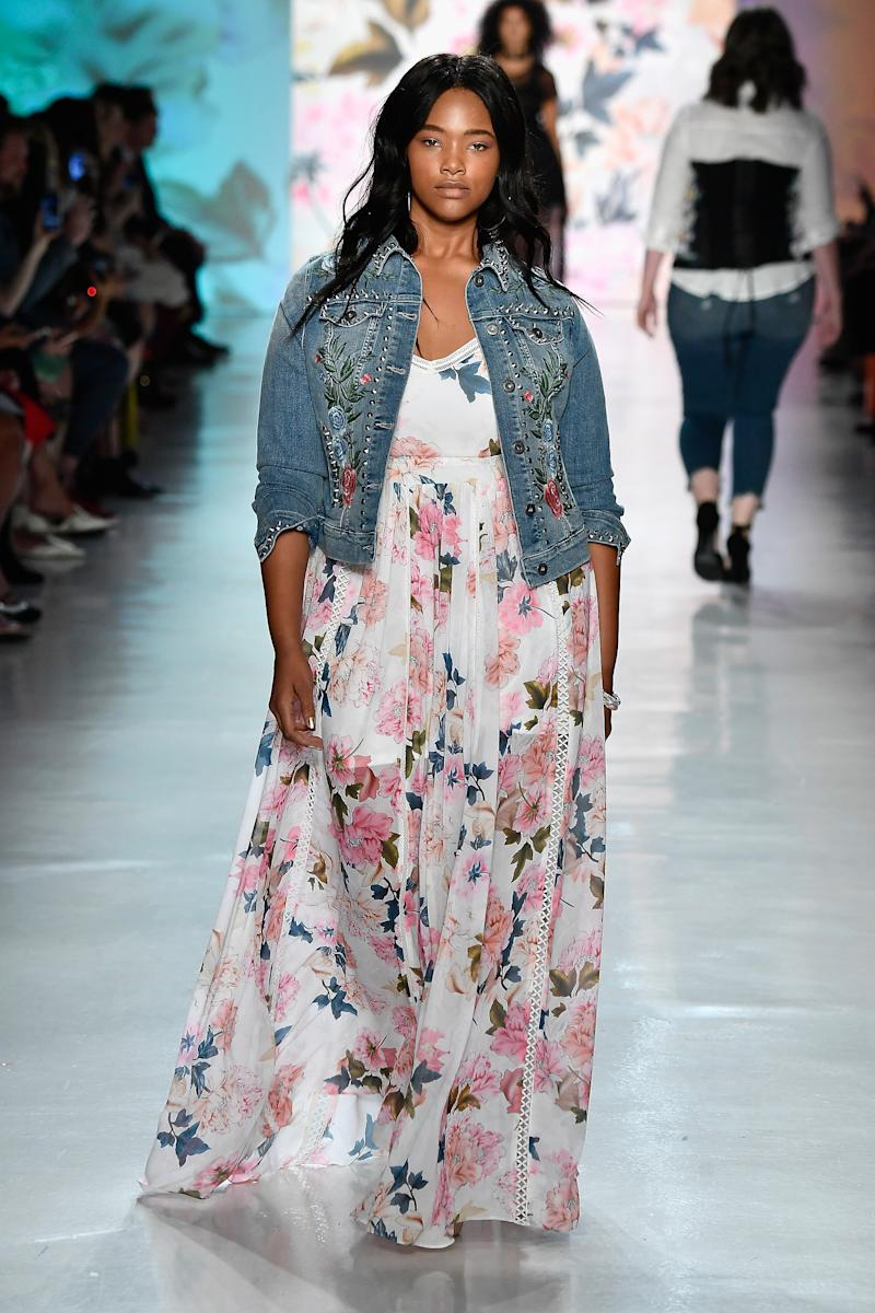 A model in an embroidered denim jacket and a floral dress at the Torrid show during NYFW.
