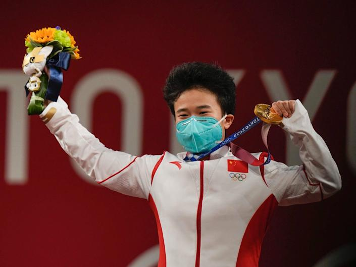 Zhihui Hou brandishes her Olympic gold medal.