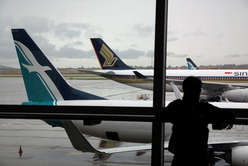 A SilkAir plane sits beside a Singapore Airlines plane at Changi Airport in Singapore