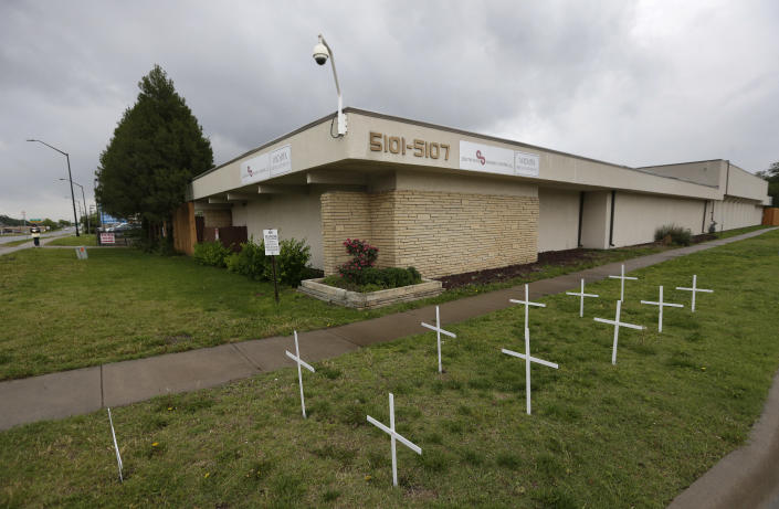FILE - In this May 19, 2016, file photo, crosses placed by anti-abortion protesters stand in the lawn outside the South Wind Women's Center in Wichita, Kan. Even before a strict abortion ban took effect in Texas this week, clinics in neighboring states were fielding more and more calls from women desperate for options. The Texas law, allowed to stand in a decision Thursday, Sept. 2, 2021 by the U.S. Supreme Court, bans abortions after a fetal heartbeat can be detected, typically around six weeks. (AP Photo/Charlie Riedel File)