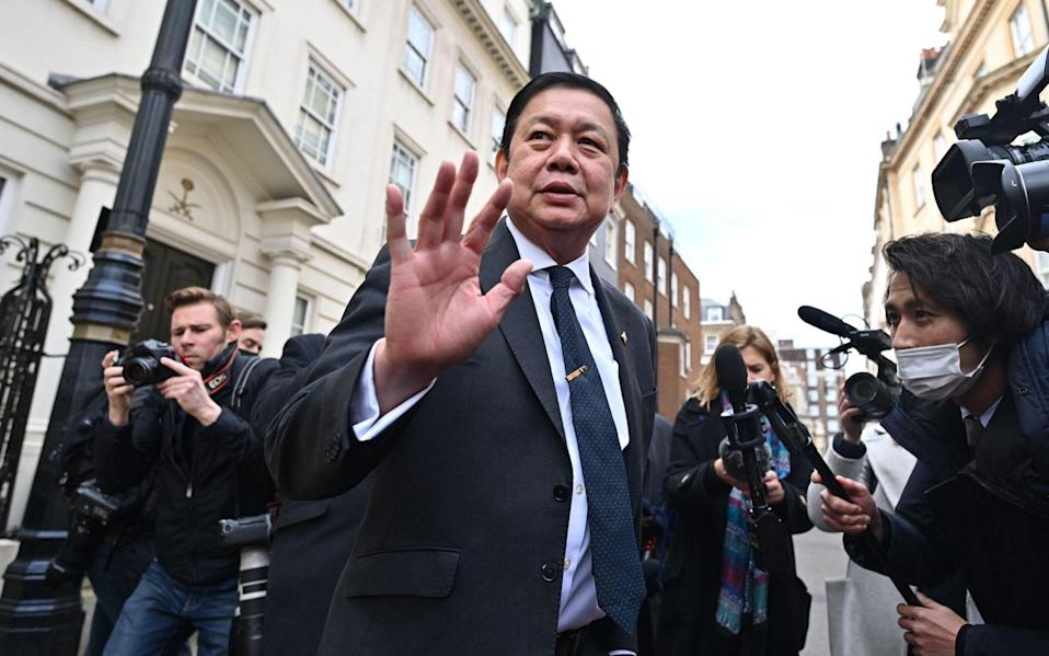 Myanmar's Ambassador to the United Kingdom, Kyaw Zwar Minn, is surrounded by members of the media on his arrival at the Myanmar Embassy in London - AFP