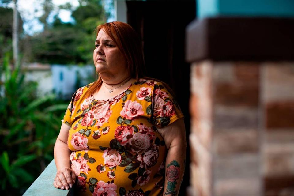 Elba Santos stands outside her house in Barranquitas, Puerto Rico, on March 21, 2021.
