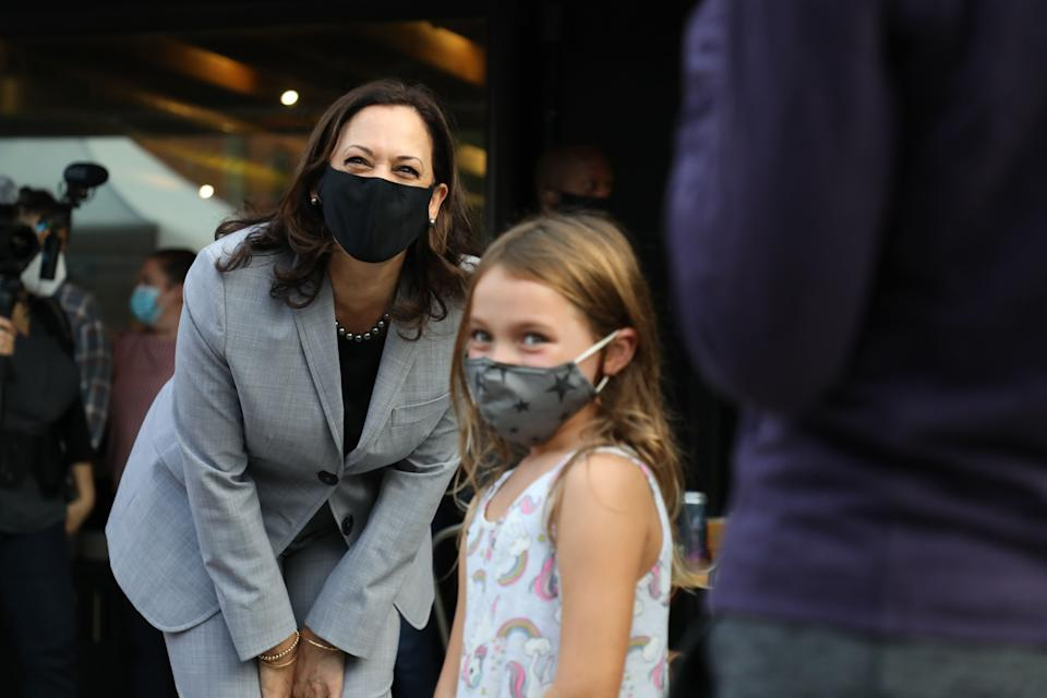 United States Senator and Democratic Vice Presidential nominee Kamala Harris greet and takes a picture with a child after greeting patrons of Trophy Brewing and Pizza at a planned campaign stop in Raleigh, North Carolina. (Photo: LOGAN CYRUS via Getty Images)