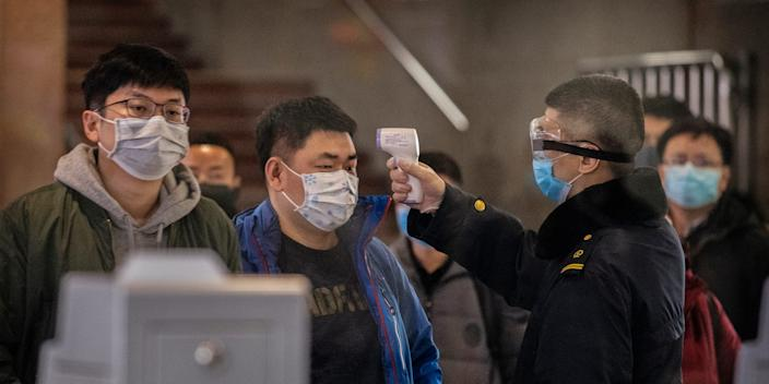 Passengers who just arrived on a train from Wuhan are screened for coronavirus in Beijing.