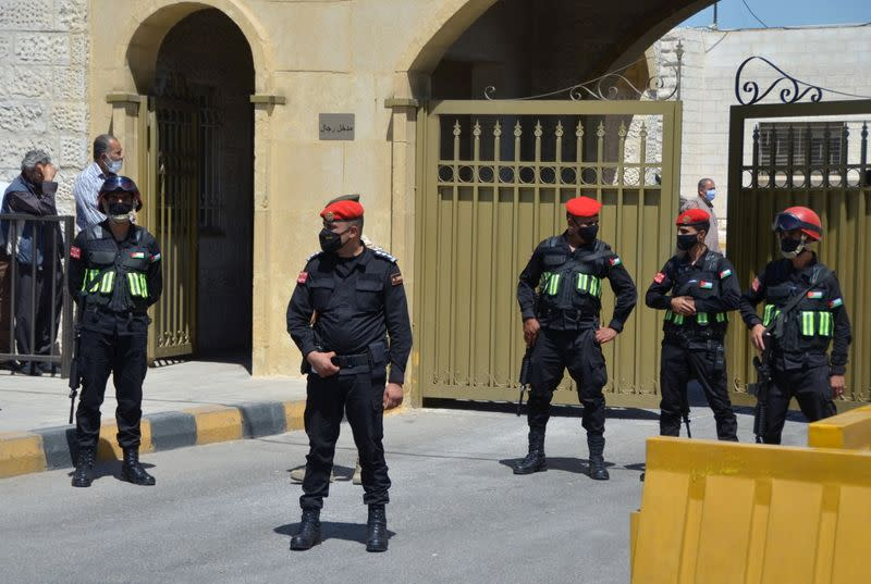 Security members stand guard outside a military court in Amman