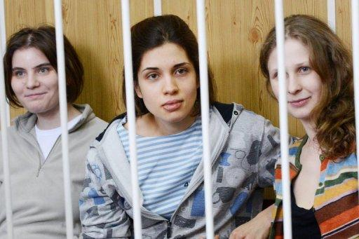 """Members of the all-girl punk band """"Pussy Riot"""" -- Nadezhda Tolokonnikova (centre), Maria Alyokhina (right) and Yekaterina Samutsevich (left), sitting behind bars during a court hearing in Moscow on July 20. They face up to seven years in a prison colony if found guilty of hooliganism"""