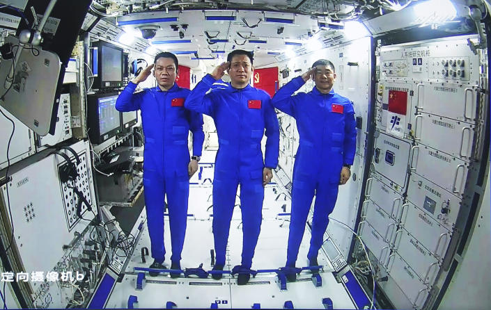 In this photo released by China's Xinhua News Agency, Chinese astronauts, from left; Tang Hongbo, Nie Haisheng, and Liu Boming salute from aboard China's space station core module Tianhe during a video conversation with Chinese President Xi Jinping, Wednesday, June 23, 2021. (Yue Yuewei/Xinhua via AP)