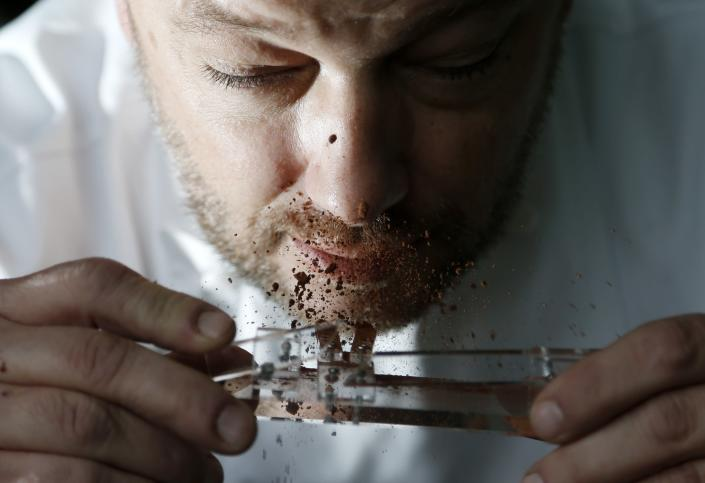 Belgian chocolatier Dominique Persoone snorts cocoa powder off his Chocolate Shooter in his factory in Bruges, February 3, 2015. When Belgian chocolatier Dominique Persoone created a chocolate-sniffing device for a Rolling Stones party in 2007, he never imagined demand would stretch much beyond the rock 'n' roll scene. But, seven years later, he has sold 25,000 of them. Inspired by a device his grandfather used to propel tobacco snuff up his nose, Persoone created a 'Chocolate Shooter' to deliver a hit of Dominican Republic or Peruvian cocoa powder, mixed with mint and either ginger or raspberry. Picture taken on February 3, 2015. REUTERS/Francois Lenoir (BELGIUM - Tags: FOOD SOCIETY)
