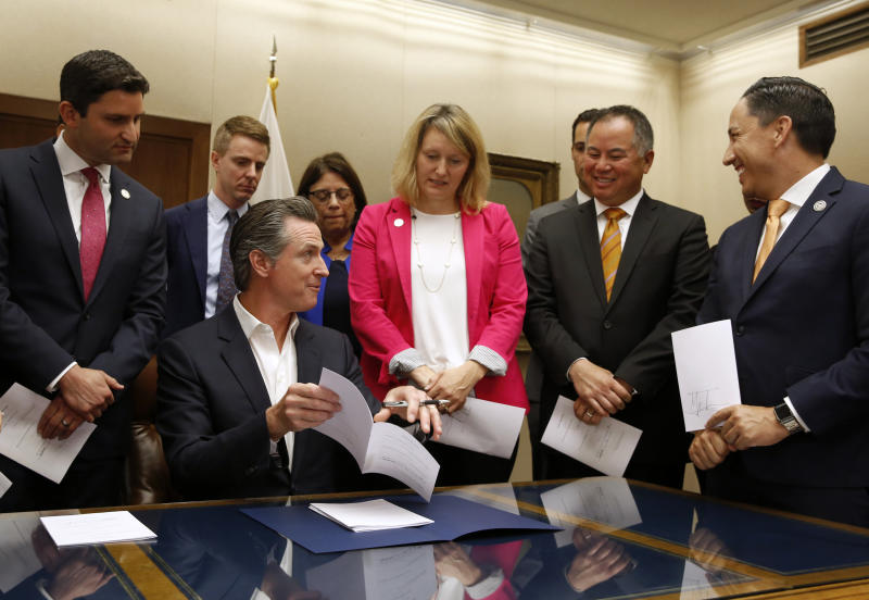California Gov. Gavin Newsom, seated, talks with Assemblyman Phil Ting, D-San Francisco, second from right, before signing Ting's measure that allows employers, co-workers and teachers to seek gun violence restraining orders for people they believe to be a danger to themselves or others, during a signing ceremony at the Capitol in Sacramento, Calif., Friday, Oct. 11, 2019. Ting's bill was one of more than a dozen gun control bills the governor signed Friday. (AP Photo/Rich Pedroncelli)