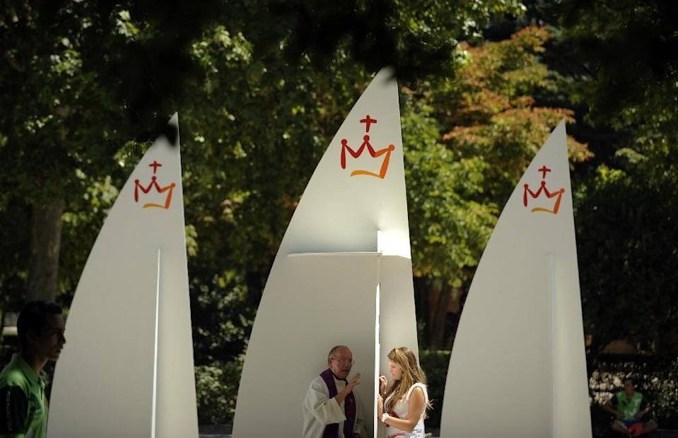 A young woman says confession to a priest at a temporary confessionals set up in Madrid (AFP Photo/PEDRO ARMESTRE)