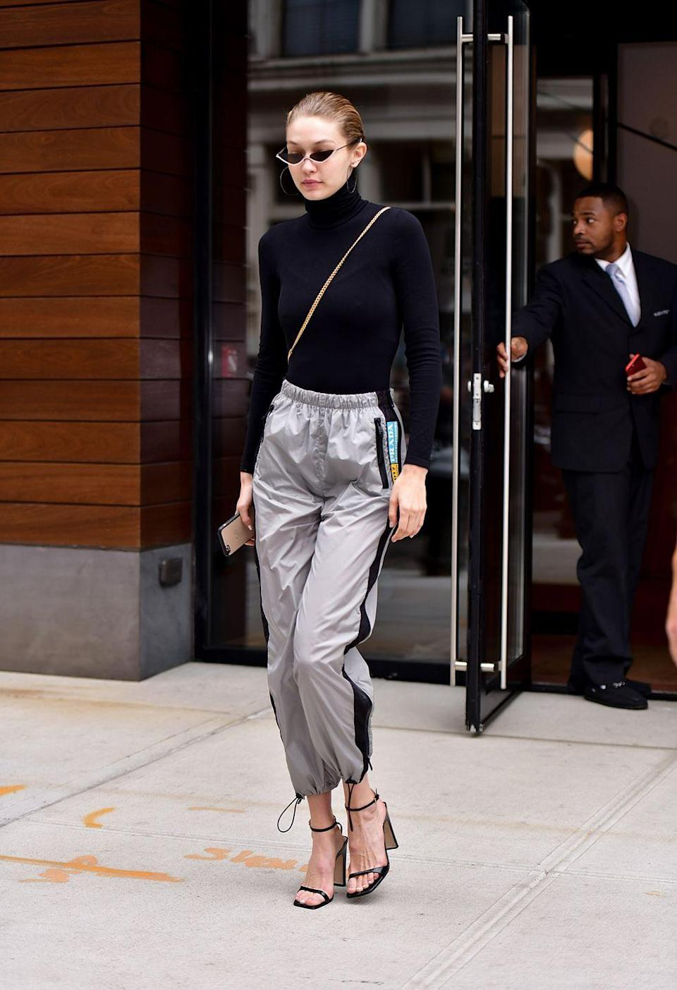 <p>Gigi just made those weird pants your 2nd grade crush used to wear look cool again. She paired her probably very loud windbreaker pants with a simple turtleneck, strappy heels, and angular shades. </p>