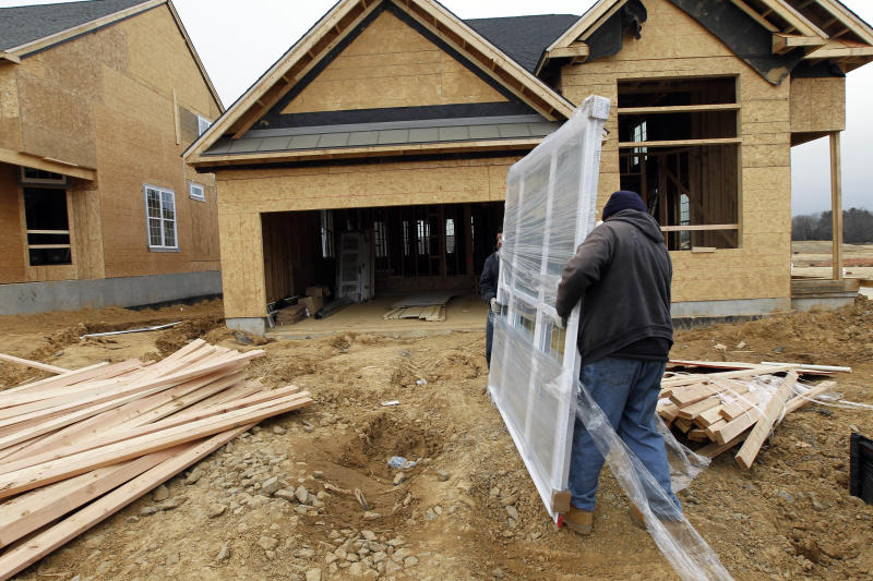 In this Feb. 8, 2012 photo, two workers carry a window for a home  under construction in a new subdivision by Toll Brothers, in Yardley, Pa. Sales of new U.S. homes dipped in January but only after the government said the final quarter of 2011 was stronger than first estimated. (AP Photo/Alex Brandon)