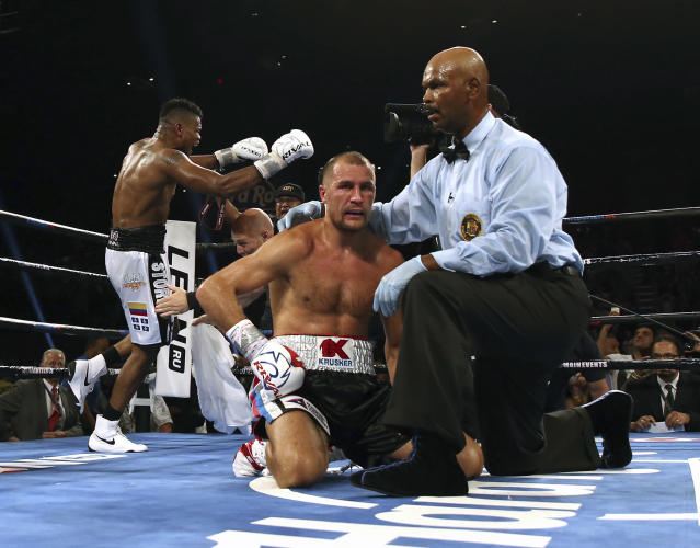 Eleider lvarez, rear, of Colombia, celebrates as referee David Fields holds on to Sergey Kovalev, of Russia, after Alvarez knocked Kovalev out during the seventh round of their boxing bout at 175 pounds, Saturday, Aug. 4, 2018, in Atlantic City, N.J. (AP Photo/Mel Evans)