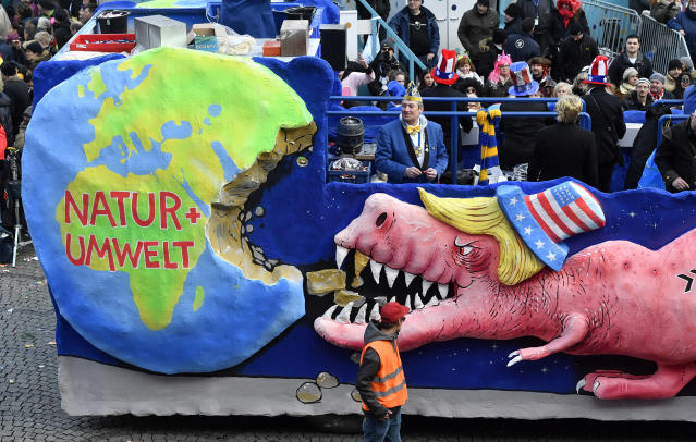 <p>A carnival float depicts a dinosaur with the U.S. flag on its hat eating a large chunk from the earth during the traditional Rose Monday parade in Duesseldorf, Germany, Shrove, Feb. 12, 2018. (Photo: Martin Meissner/AP) </p>