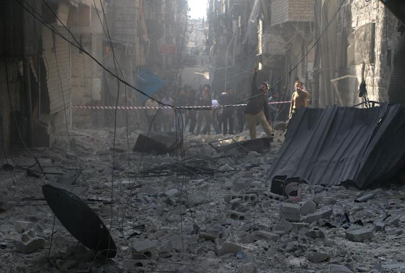 Syrians stand in a street filled with debris following a reported barrel bomb attack by government forces in the northern city of Aleppo, on October 31, 2014 (AFP Photo/Baraa al-Halabi)