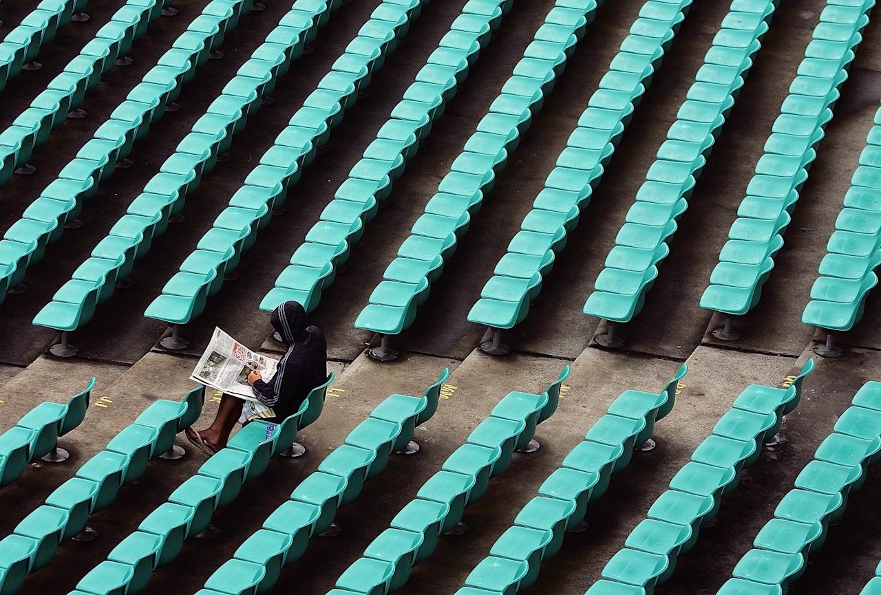 SYDNEY, NSW - JANUARY 05:  A spectator reads the paper during a rain delay during day four of the Third Test between Australia and South Africa at the Sydney Cricket Ground January 5, 2006 in Sydney, Australia.  (Photo by Cameron Spencer/Getty Images)