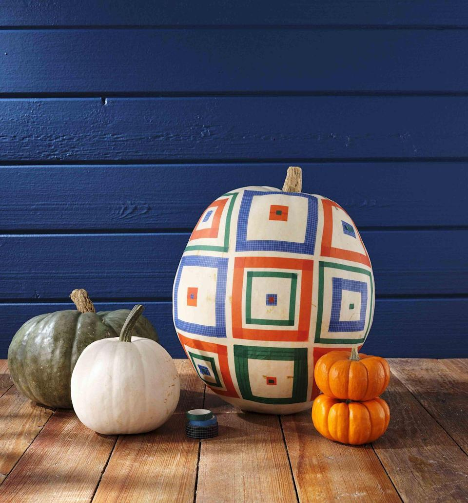 <p>Modern quilt squares made from washi tape come together to make this oh-so-country pumpkin.<strong><br></strong></p><p><strong>Make the pumpkin:</strong> Starting in the center of a large white pumpkin, cut lengths of washi tape to create a square. Use a thinner width of a second color of tape to make another square within the first one. Add a square of tape in the center, and top with a smaller square. Continue making squares, varying the designs as you go. </p>