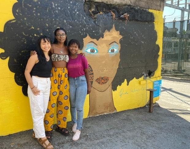 Three of the Black Stratchona Resurgence Project artists, Paige Jung, Rachel Achus and Enia Sitole stand beside Sitole's completed mural near Main and Keefer in Vancouver. (Jennifer Wilson/CBC News - image credit)