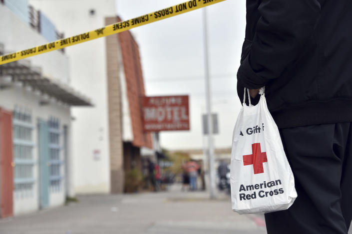 A displaced resident carries a bag from the Red Cross after a fire at a three-story apartment complex early Saturday, Dec. 21, 2019 in Las Vegas. The fire was in first-floor unit of the Alpine Motel Apartments and its cause was under investigation, the department said. Authorities say multiple fatalities were reported and many more were injured. (AP Photo/David Becker)