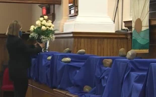 At the church, roses were placed next to rocks bearing the names of the victims.